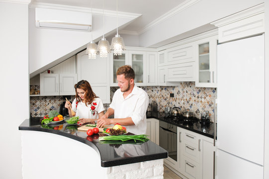 young vegan family husband and wife cooking fresh food vegetables in kitchen