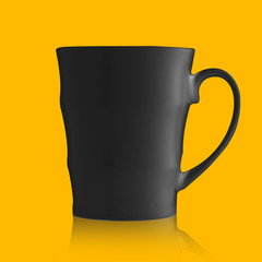 Black porcelain mug isolated on orange background