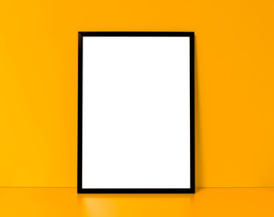 Blank black framed poster on a yellow interior background, mock up