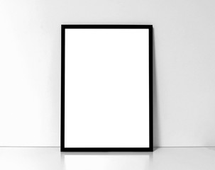 Blank black framed poster on a white interior background, mock up