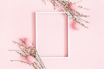 Easter composition. Easter eggs, photo frame, white flowers on pastel pink background. Flat lay, top view, copy space