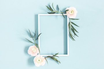 Flowers composition. White flowers, eucalyptus leaves, photo frame on pastel blue background. Flat lay, top view, copy space