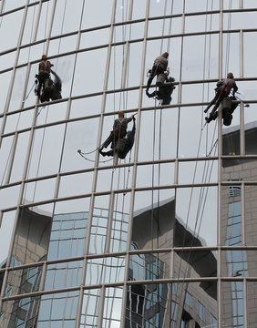 Office buildings are reflected in the windows of a building as workers clean its facade in Beijing