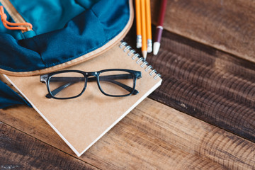 school bag, notebook,pencil,pen and eyeglasses on a wooden table.concept of school equipment and...