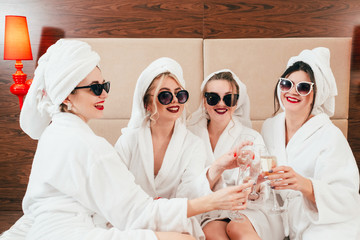 Bachelorette party fun. Cheerful young females in sunglasses, bathrobes and towel turbans clinking champagne glasses.