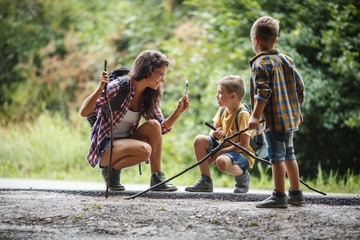 Mother and her little sons hiking trough forest .They using magnifying glass and looking at insects.