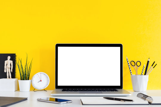 Laptop on desk stationery, succulent, clock and yellow wall for copy space.