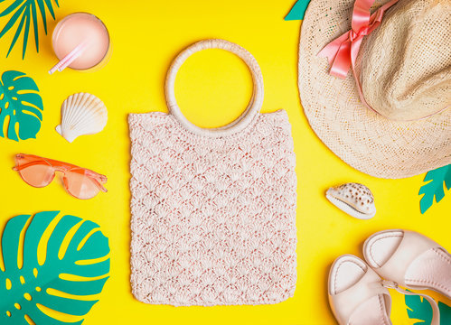 Summer female outfit. Flat lay.  Woven hand bag, straw hat, sunglasses, sandals with cocktail , seashells and tropical paper palm leaves on yellow background, top view. Summer holiday vacation.