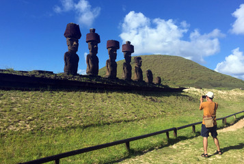"A tourist take a picture of statues named ""Moai"" at Easter Island"