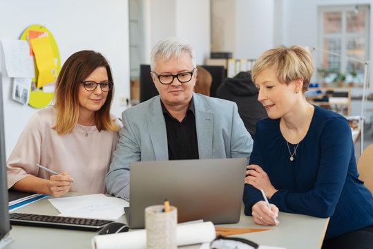 Three businesspeople gathered around a laptop
