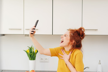 Young woman screaming or singing with smartphone