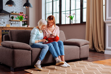 Elderly female sitting on sofa with her young-adult daughter