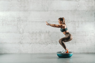 Side view of muscular Caucasian woman in sportswear and with ponytail doing squat endurance on bosu ball. In background wall.