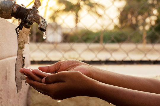 Closeup of hands, child drinking water directly from corporation tap water in India