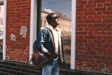 Wall Mural - Happy smiling african man in jeans jacket, with backpack looking up at sunlight walking on city street over brick wall background