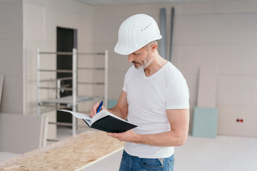 Builder making construction notes on a new build