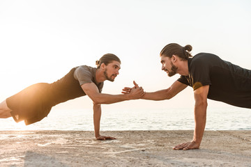 Two twin brothers doing exercises at the beach together