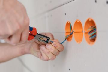 Handyman stripping an electric wire