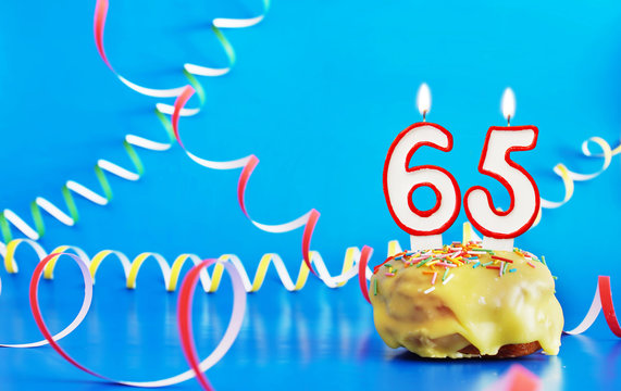 Birthday of sixty five years. Cupcake with white burning candle in the form of number 65. Vivid blue background with copy space