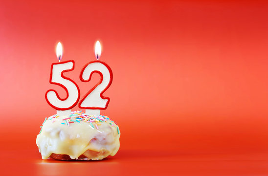 Fifty two years birthday. Cupcake with white burning candle in the form of number 52. Vivid red background with copy space