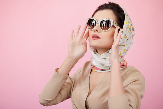 Stylish confident brunette woman touching his sunglasses, wearing in scarves, looking up, isolated on a pink background.