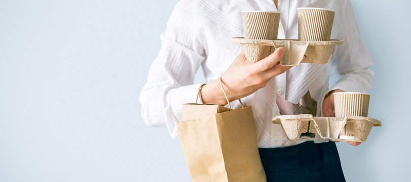 Female holding coffee containers, paper bag withfood containers. Food and coffee delivery. Intern on first job