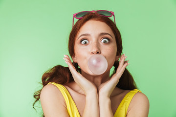 Redhead girl posing isolated over green wall background with chewing gum.