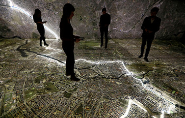 """Museum staff members walk with mobile devices over a giant illuminated aerial photograph of Berlin at the exhibition """"The Stasi in Berlin"""" inside former Stasi prison in Berlin"""
