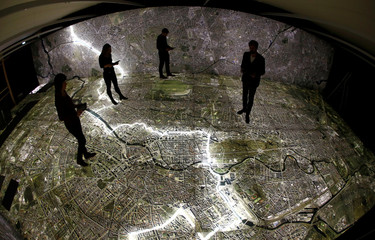 """Museum staff members walk with mobile devices over a giant illuminated aerial photograph of Berlin at the exhibition """"The Stasi in Berlin"""" inside former Stasi prison, in Berlin"""
