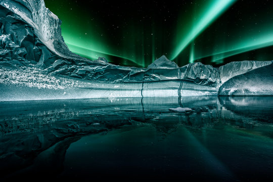 iceberg floating in greenland fjord at night with green northern lights