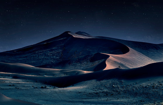 desert of namib at night with orange sand dunes and starry sky
