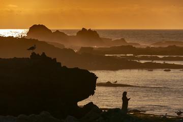 Fototapeta Marokańska kobieta robi sobie selfie na brzegu oceanu o zachodzie słońca obraz