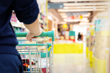 female shopper with trolley with blurred motion of supermarket department store