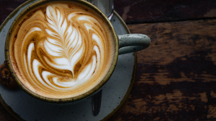 Top down shot of a perfectly made cappuccino made with locally grown coffee with a latte art rosetta on a worn wooden table framed to the left with a blurry background Wall mural
