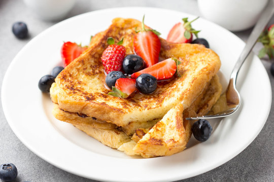French toast with berries (blueberries, strawberries) and sauce, traditional sweet dessert of bread with egg and milk. Morning baking food
