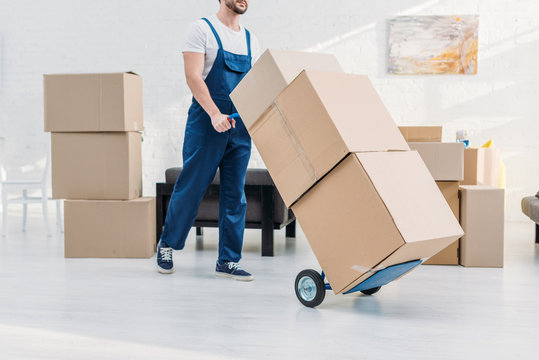 cropped view of mover in uniform transporting cardboard boxes on hand truck in apartment