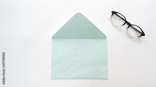 Wall mural Office desk table with  envelope and glasses close up Top view copy space