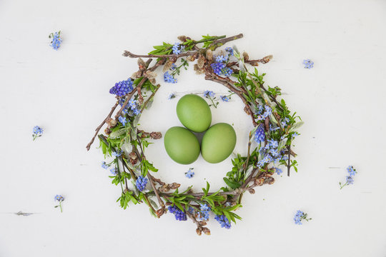 Self-made Easter wreath and green dyed eggs on white ground