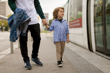 Father and son walking hand in hand at tram stop in the city