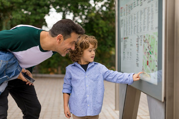 Smiling father and son looking at map in the city