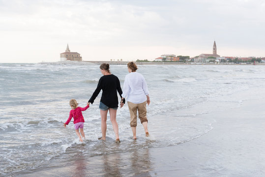 Italy, Caorle, two women walking with girl at the waterfront
