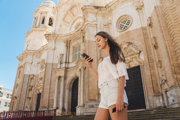 Tourist girl traveling alone, looking for something in the smartphone on the background of the ancient cathedral in Europe. looks into the navigator