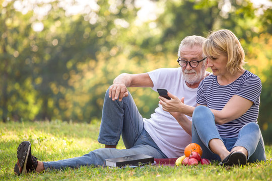Happy senior couple relaxing in park using smartphone together . old people sitting on grass in the summer park looking mobile phone . Elderly resting .mature relationships