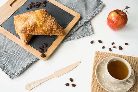 flat lay tea time with traditional Dutch food appelflap, apple turnover, fruit, mug, knife, on wooden background