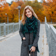 Young happy woman with a beautiful smile with blond hair in trendy elegant clothes with a handbag is standing on a vintage bridge in an autumn park with yellow trees. Positive girl enjoys the weekend.