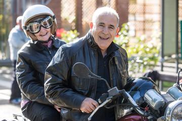 Coppia di anziani vanno in giro sulla loro Motocicletta  d'epoca Wall mural