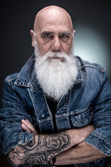 studio portrait of a bald man with tattooed arms and white beard