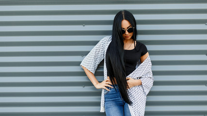 Young American hipster woman with long hair in round sunglasses in a black fashionable top in a light summer jacket in vintage jeans is standing near a gray metal wall. Urban girl relaxes.Street style