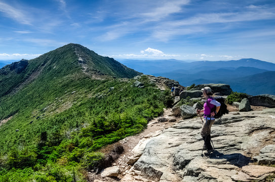 Hking woman standing on Franconia ridge, looking afar on a warm summer day, New Hampshire, USA