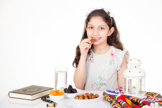 Happy young Muslim girl eating dates for iftar - breakfast in holy Ramadan